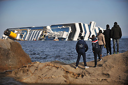 "Residents stand and watch the  Wrecked Cruise Ship ""Costa Concordia"" in Giglio, Italy, as the ship starts to move. Photo By Nick Cornish/ I-Images."
