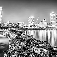 Milwaukee skyline at night black and white photo. High resolution picture includes the Milwaukee lakefront, U.S. Bank Center skyscraper, Milwaukee Art Museum, University Club Tower building, Northwestern Mutual Tower building, and breakwall rocks.