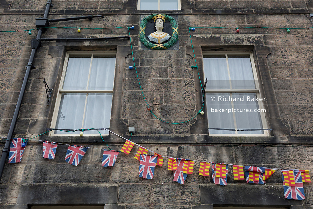 The exterior of the Queen's Head pub with Union Jack bunting and the colours of the county of Northumberland, on 25th September 2017, in Rothbury, Northumberland, England.
