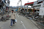 A man walks through the rubble strewn streets after the tsunami that struck the north east coast of Japan on March 11th. Kamaishi, Iwate, Japan. March 17th 2011