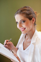 Portrait of young woman writing notes on spiral notebook