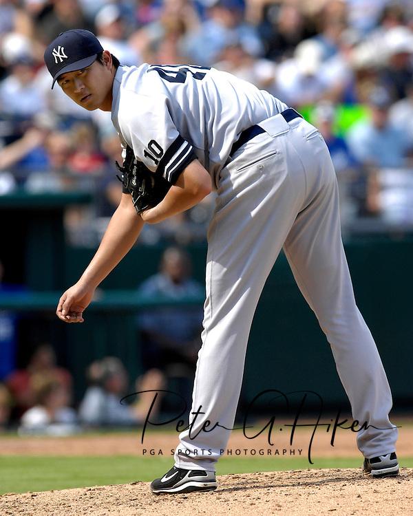 New York Yankees pitcher Chien-Ming Wang checks the runner at first base during a game against the Kansas City Royals at Kauffman Stadium in Kansas City, Missouri....