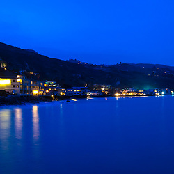 Malibu California coastline at night panorama photo in blue. Malibu is a coastal city along the Pacific Ocean in Southern California in the United States. Panoramic photo ratio is 1:3. Copyright ⓒ 2015 Paul Velgos with All Rights Reserved.