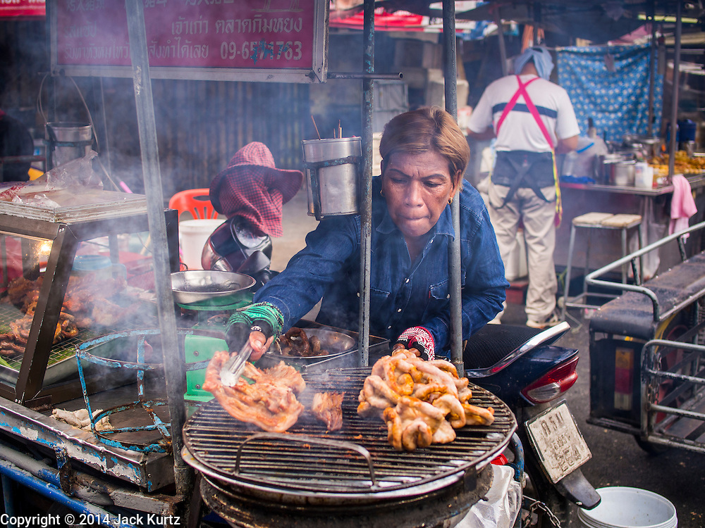 29 JULY 2014 - HAT YAI, SONGKHLA, THAILAND:  A street vendor grills meat in Hat Yai, Thailand. Hat Yai is the 4th largest city in Thailand and the largest outside of the Bangkok metropolitan area. It's less the 50 miles from the Malaysian border and is a popular vacation spot for Malaysian and Singaporean tourists.       PHOTO BY JACK KURTZ