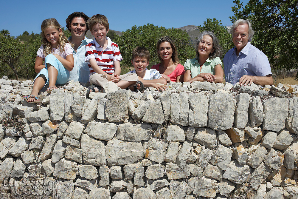 Portrait of three-generation family with three children (6-11) by stone wall