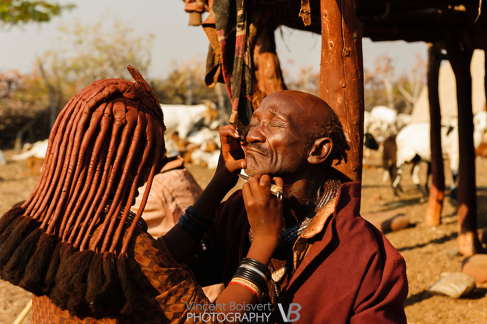 A young himba woman shaving his father, the chief of the vilage