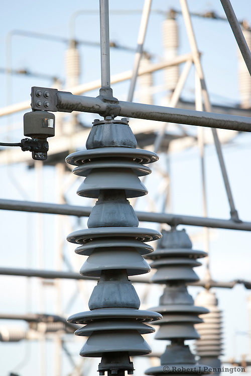 Insulators, switches and conductors at an electrical utility substation.