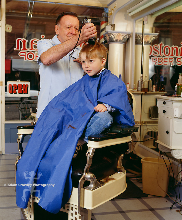 Boy (4-5) having haircut by male barber