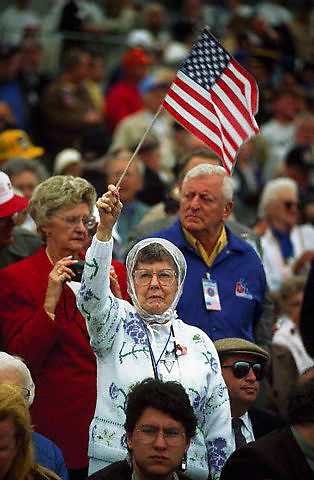 06 Jun 1994, France --- A woman in the crowd waves an American flag during the 50th anniversary of D-Day at Omaha Beach, France. --- Image by © Owen Franken/Corbis