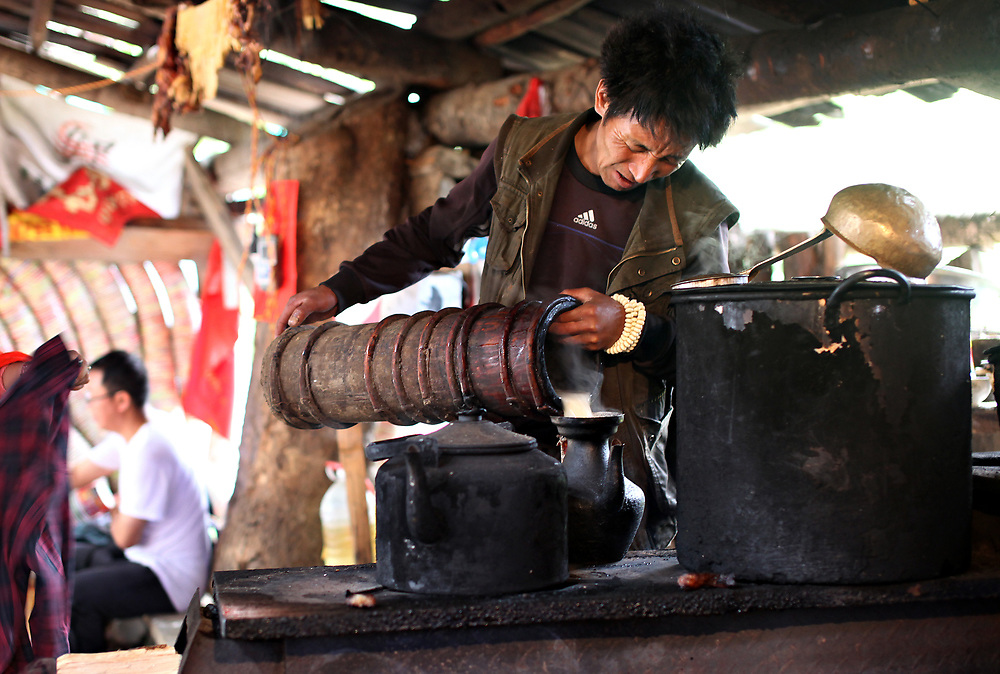 A man pours churned  butter tea into a kettle at a trailside hut between Xidang and Yubeng, Yunnan, China; September, 2013.