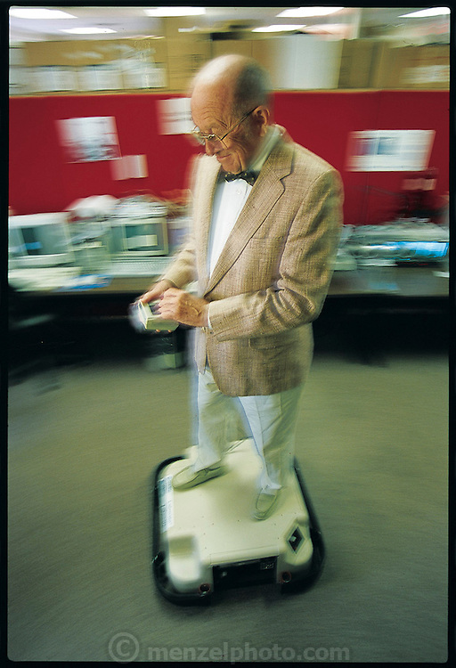 Known as the founder of modern industrial robotics, 74-year-old Joseph Engelberger hitches a ride around his workplace on LabMate. A now-standard platform that companies use for a variety of autonomous robots, LabMate is manufactured by HelpMate, the Danbury, CT company Engelberger founded in 1984. (He sold the company in 1999 to Pyxis, a subsidiary of Cardinal Health, a health-maintenance organization in Ohio, but remains there as a consultant.) Engelberger's interest in robotics dates back to his days as a physics and engineering student. In the 1960s he founded Unimation, the first company that made large robots for automobile factories. Recently Engelberger has devoted more of his energies to making robots that can move about and interact with people, the focus of HelpMate. From the book Robo sapiens: Evolution of a New Species, page 187.