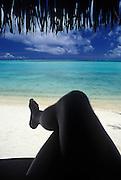 Image of a man sitting under a palapa in Bora Bora, Tahiti, French Polynesia, model released