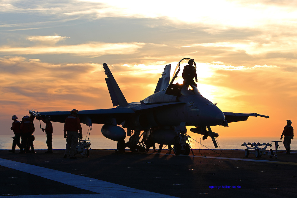 A Boeing F/A-18C Hornet, AC 314 165184 from the VFA-37 'Bulls' recieves some TLC between missions on the deck of CVN-75 USS Harry S. Truman at sunset.