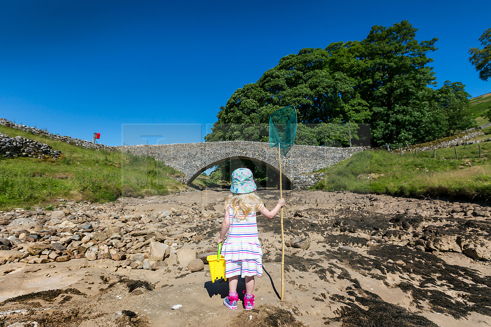 © Licensed to London News Pictures. 03/07/2018. Yockenthwaite UK. Three year old Scarlet stands on the dried up river bed of the River Wharfe with her fishing net & bucket in the village of Yockenthwaite, Yorkshire Dales, as the UK heatwave continues & a hosepipe ban looks imminent. Photo credit: Andrew McCaren/LNP