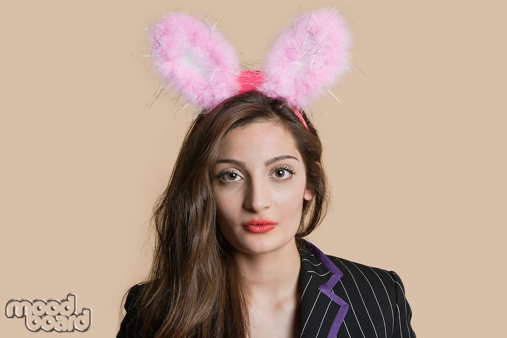Portrait of a beautiful young woman wearing bunny ears over colored background