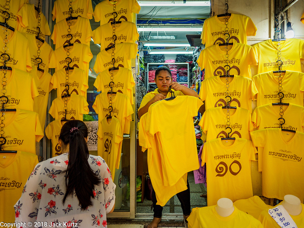 "03 JULY 2018 - BANGKOK, THAILAND: A woman buys yellow shirts that say ""Long Live the King"" from a vender in Bobae Market in Bangkok. The birthday of King Maha Vajiralongkorn Bodindradebayavarangkun, Rama X, is 28 July. The King, the only son of Thailand's late King Bhumibol Adulyadej, became the King of Thailand in 2016 after the death of his father. King Vajiralongkorn was born on 28 July 1952, a Monday. In Thai culture each day of the week has a color, and yellow is the color is associated with Monday, so people wear yellow for the month before his birthday to honor His Majesty.    PHOTO BY JACK KURTZ"