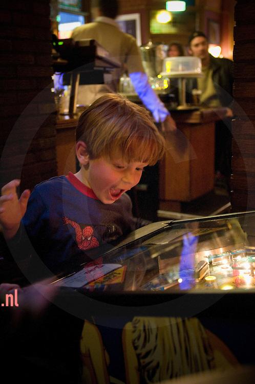 Een jongen speelt aan een flipperkast in café het bolwerk in enschede. stadsgravenstraat
