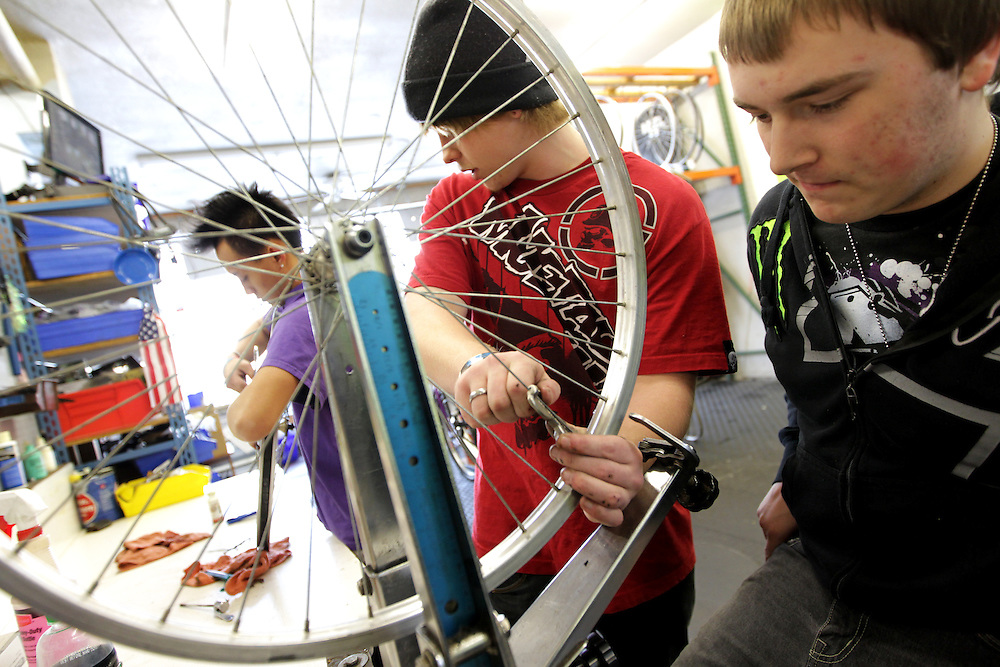 Ty Spangle, 17, center, shows apprentice Marcus Wachholz, 17, right, how to replace a spoke on a refurbished bicycle at Express Bike Shop in St. Paul, Minnesota.  Formerly a Youth Express apprentice, Spangle is now a mechanic at the shop, teaching skills to new program participants. .
