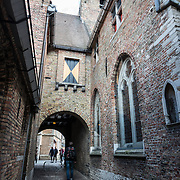 The exterior of the historic Old St. John's Hospital in Bruges, Belgium. Old St. John's Hospital is one of Europe's oldest surviving hospital buildings that dates to the 11th century. It originally treated sick pilgrims and travelers. A monastery and convent was later added. It is now a museum.