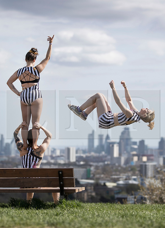 © Licensed to London News Pictures. 17/04/2018. London, UK. Members of 'No Show' all female acrobatic troupe perform in sight of the London skyline from Parliament Hill in warm afternoon sunshine. 'No Show'  and 'The Bekkrell Effect' all female troupes are performing in the third week of CircusFest at The Roundhouse in Camden. Photo credit: Peter Macdiarmid/LNP
