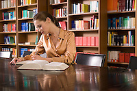 Young woman reading book at desk in library