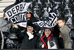 Derby County fans in the stands wave flags to show their support