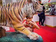 16 NOVEMBER 2013 - BANGKOK, THAILAND: A girl makes an offering at the statue of a tiger at the Wat Saket Temple Fair in Bangkok. Wat Saket is on a man-made hill in the historic section of Bangkok. The temple has golden spire that is 260 feet high which was the highest point in Bangkok for more than 100 years. The temple construction began in the 1800s in the reign of King Rama III and was completed in the reign of King Rama IV. The annual temple fair is held on the 12th lunar month, for nine days around the November full moon. During the fair a red cloth (reminiscent of a monk's robe) is placed around the Golden Mount while the temple grounds hosts Thai traditional theatre, food stalls and traditional shows.     PHOTO BY JACK KURTZ