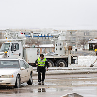 Gallup Police officer Andrea Tsosie inspects a Ford Thunderbird abandoned on North 9th Street as city workers tend to a pole the car hit in Gallup Monday.