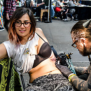 Fiumax & Kila tattoo, Tattoo a client at The Great British Tattoo Show, on 26 May 2019, London, UK.