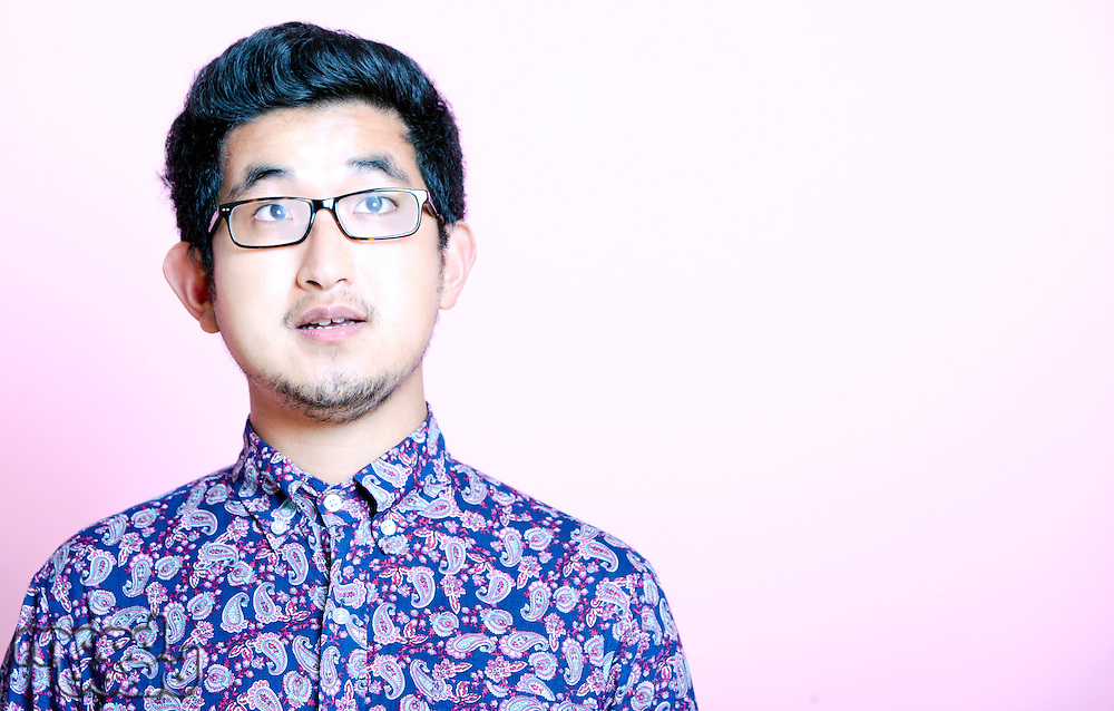Young Geeky Asian Man in colorful shirt wearing glasses