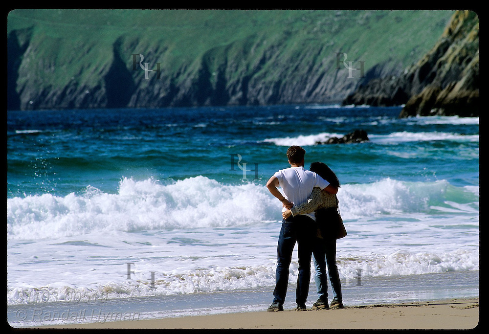 Young lovers embrace while admiring the chilly surf of Coumeenole Beach near Dunmore Head on the Dingle Peninsula; Ireland.