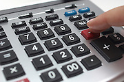 Person using calculator, close-up of finger