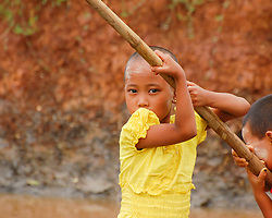 A young girl in Burma (Myanmar) looks intently from her longtail boat