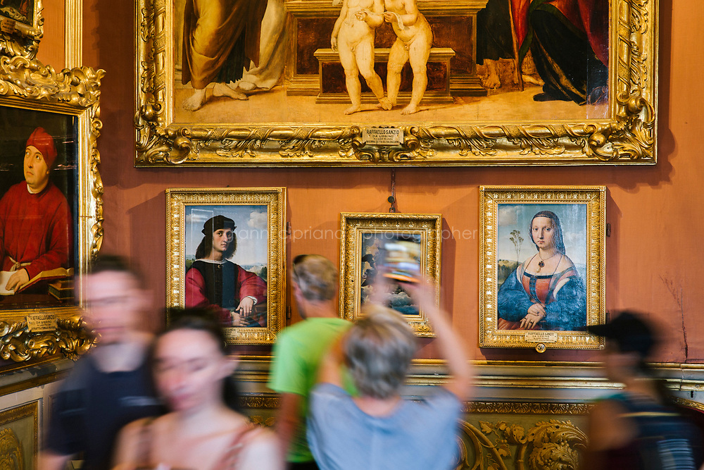 FLORENCE, ITALY - 3 JUNE 2018: A visitor are seen here by the dual portraits of Agnolo Doni and his wife Maddalena Strozzi, painted by Raphael round 1504-1505, here in the Hall of Saturn of Palazzo Pitti before the paintings will be relocated in room 41 of the Uffizi, in Florence, Italy, on June 3rd 2018.<br /> <br /> As of Monday June 4th 2018, Room 41 or the &ldquo;Raphael and Michelangelo room&rdquo; of the Uffizi is part of the rearrangement of the museum's collection that has<br /> been defining Uffizi Director Eike Schmidt&rsquo;s grander vision for the Florentine museum.<br /> Next month, the museum&rsquo;s Leonardo three paintings will be installed in a<br /> nearby room. Together, these artists capture &ldquo;a magic moment in the<br /> first decade of the 16th century when Florence was the cultural and<br /> artistic center of the world,&rdquo; Mr. Schmidt said. Room 41 hosts, among other paintings, the dual portraits of Agnolo Doni and his wife Maddalena Strozzi painted by Raphael round 1504-1505, and the &ldquo;Holy Family&rdquo;, that Michelangelo painted for the Doni couple a year later, known as the<br /> Doni Tondo.