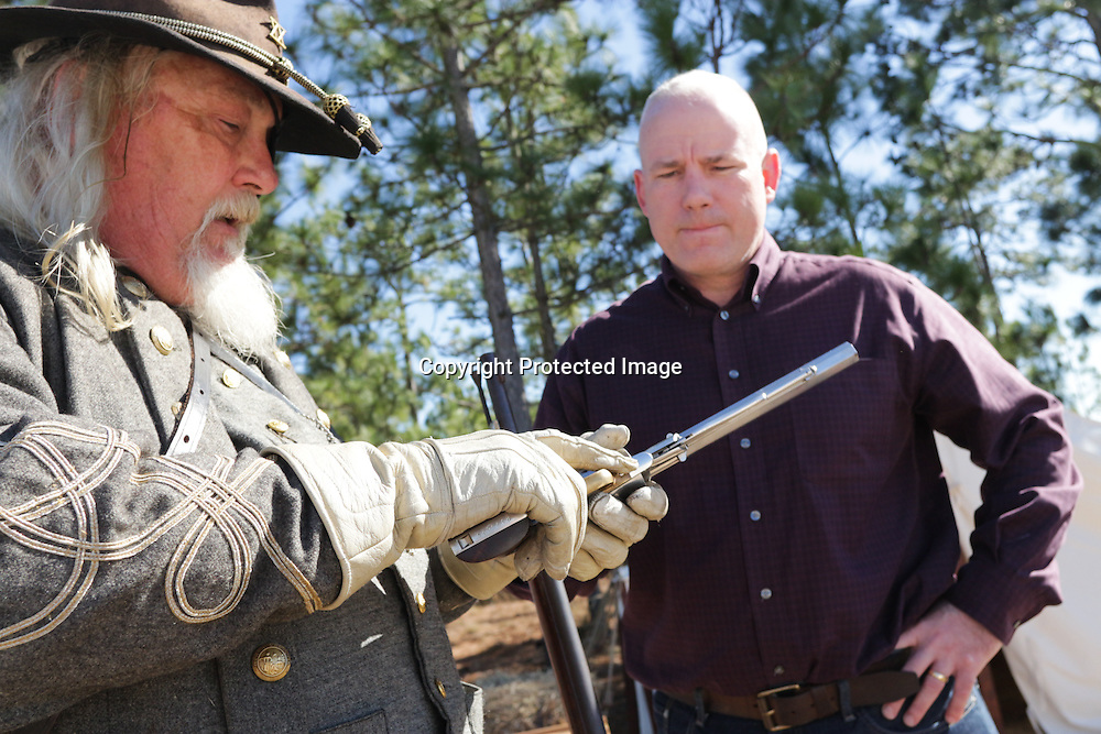 Reenactor Capt. Derrick Smith wight he 20th K N.C. State Troopers demonstrates a pistol for Mark Blanchard Sunday February 8, 2015 during the 10th Annual Civil War Living History Weekend at Cameron Art  Museum. The Weekend commemorated the Battle of Forks Road. (Jason A. Frizzelle)