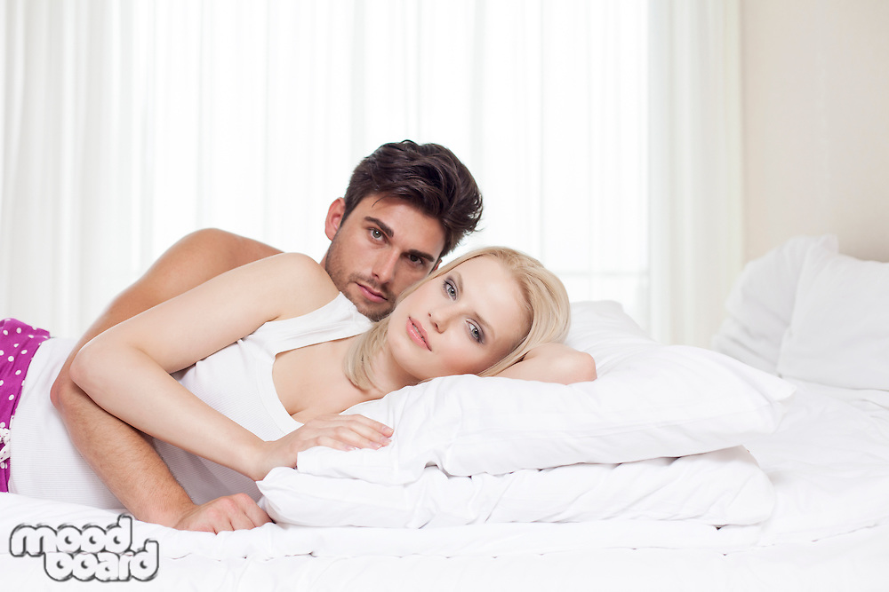 Portrait of young couple lying in bed