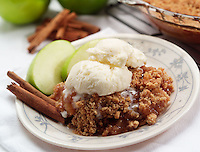 Warm apple cobbler with vanilla ice cream and apple slices