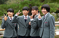 Japanese school girls dressed in uniforms posing for a photo on the grounds of the Golden Pavilion, Tokyo, Japan