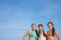 Three teenage girls (16-17) wearing bikinis pictured against sky portrait