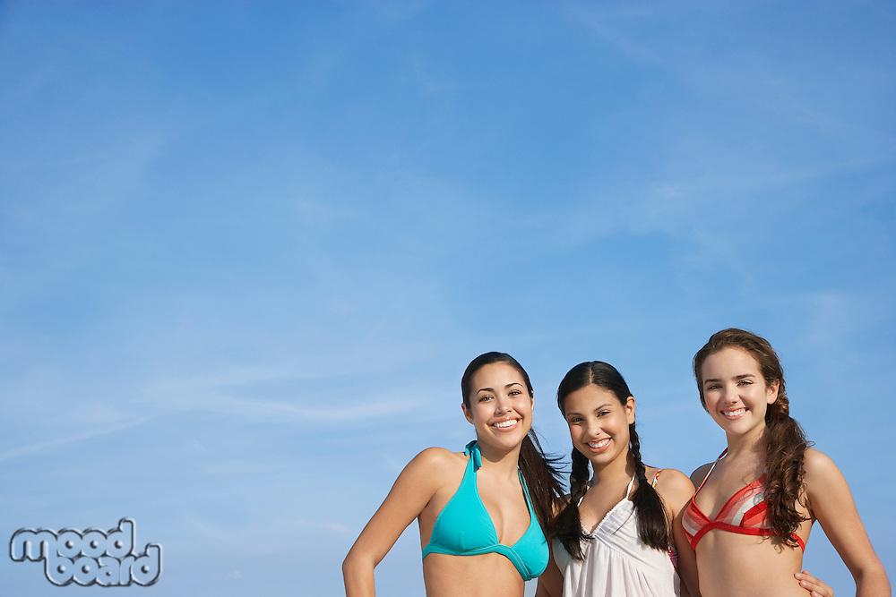 Three teenage girls (16-17) wearing bikinis pictured against sky portrait