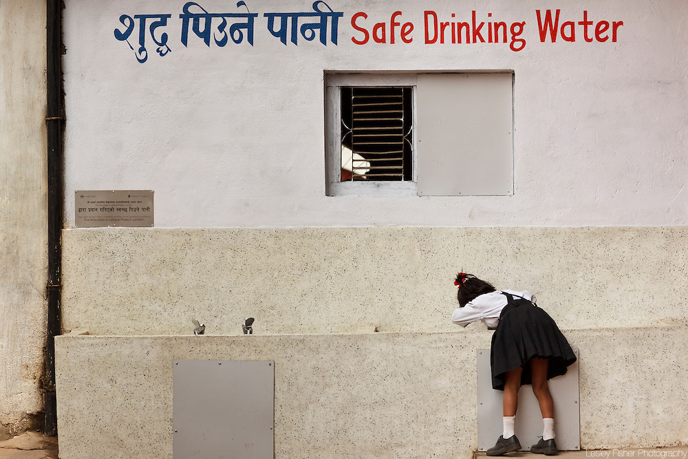 A young schoolgirl drinking from the clean drinking water installation supplied by a child's right, Adarsha Higher Secondary School, Kathmandu Metropolitan City, Kathmandu, Nepal