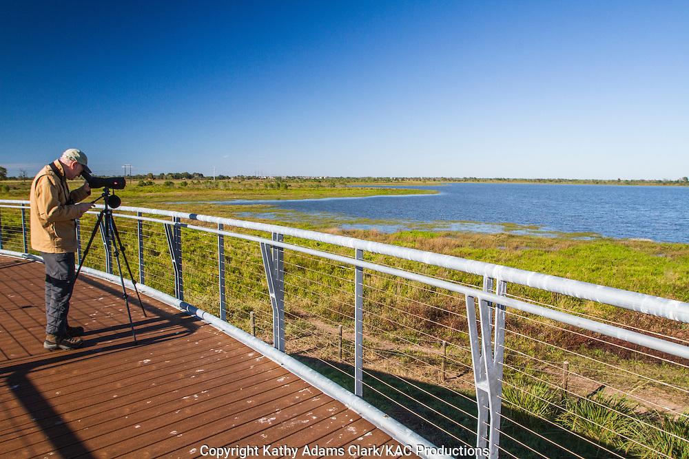 Birdwatcherer peering through a spotting scope at the Matt Cook Wildlife Viewing Platform at  Katy Prairie, in west Harris County, Texas.