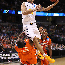 Mar 17, 2011; Tampa, FL, USA; West Virginia Mountaineers guard Joe Mazzulla (21) draws a foul on a shot from Clemson Tigers guard Andre Young (11) during the second half of the second round of the 2011 NCAA men's basketball tournament at the St. Pete Times Forum. West Virginia defeated Clemson 84-76.  Mandatory Credit: Derick E. Hingle