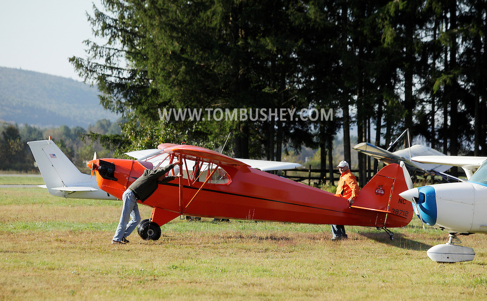 Wurtsboro, New York - Two men push a Piper Cub airplane into position at Wurtsboro Airport during the annual Fly In - Drive- In Breakfast on Oct. 9, 2011.