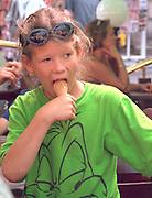 Girl age 10 devouring ice cream cone in sidewalk cafe.  Warsaw Poland