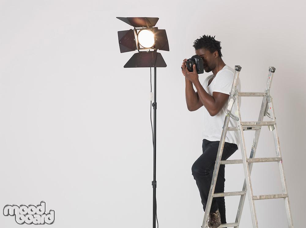 Mid adult (30-35 years) photographer in studio