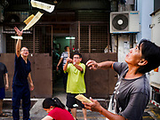 24 AUGUST 2018 - GEORGE TOWN, PENANG, MALAYSIA: A man throws ghost money into the air during Hungry Ghost Month in George Town. The Ghost Festival, also known as the Hungry Ghost Festival is a traditional Buddhist and Taoist festival held in Chinese communities throughout Asia. The Ghost Festival, also called Ghost Day, is on the 15th night of the seventh month (25 August in 2018). During Ghost Festival, the deceased are believed to visit the living. In many Chinese communities, there are Chinese operas and puppet shows and elaborate banquets are staged to appease the ghosts.      PHOTO BY JACK KURTZ