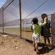 TIJUANA, MEXICO  5/15/04--A little girl in Mexico talks through the fence with her cousins on The U.S. side of the border.  Families separted by the border come to Friendship Park, the only place in Tijuana, where they can see and talk with family members.<br />                      &copy;  2004  Christopher J. Morris Immigration along the USA-Mexico border.