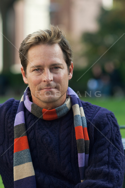 Portrait of a man in a sweater and striped scarf.
