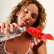 Sasha B. tries to get a toy fish to drink water from a  bottle.